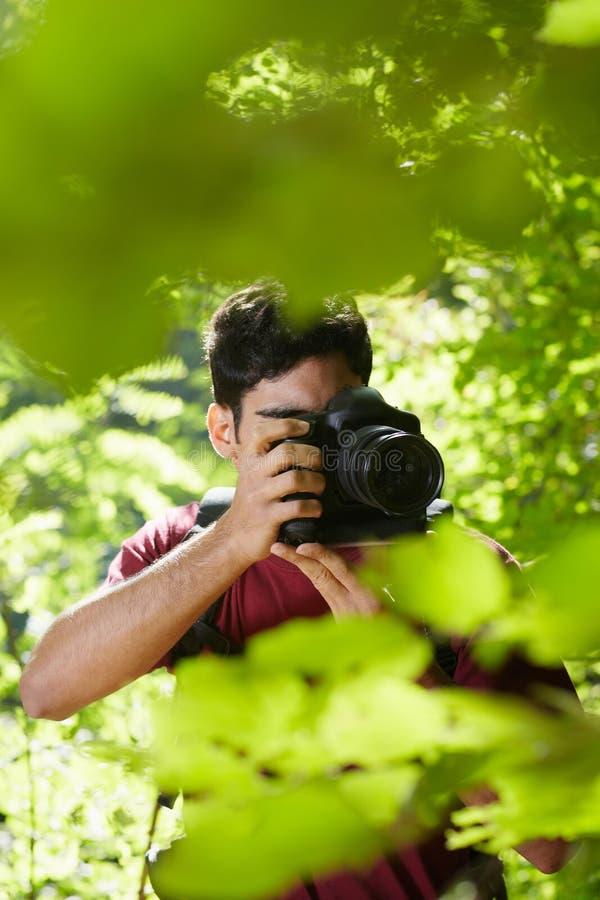 Fotógrafo de sexo masculino joven que va de excursión en bosque foto de archivo libre de regalías