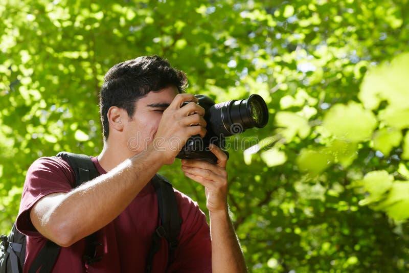 Fotógrafo de sexo masculino joven que va de excursión en bosque imagen de archivo libre de regalías