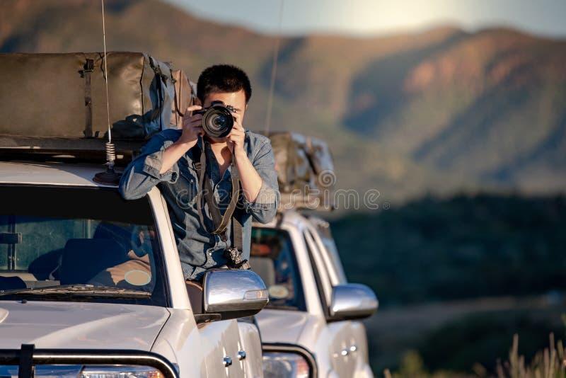 Fotógrafo de sexo masculino que toma la foto en la ventanilla del coche fotografía de archivo