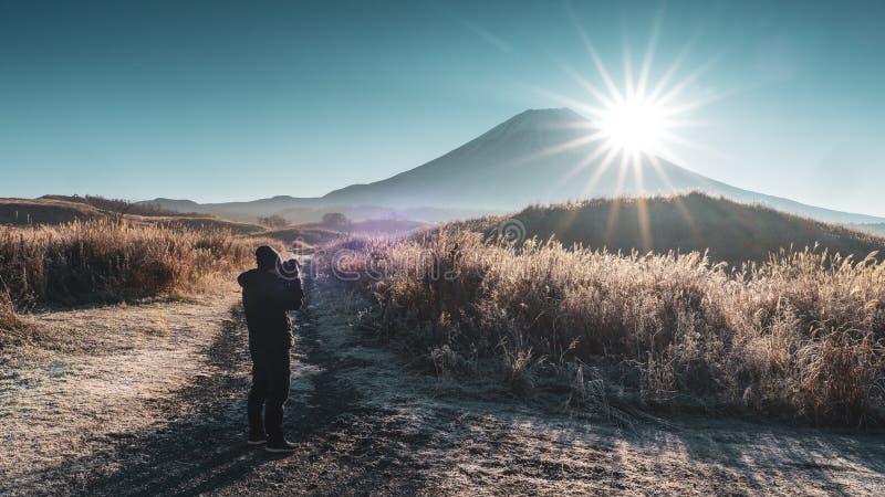 Fotógrafo de sexo masculino que toma las fotos en un ajuste hermoso de la naturaleza Fotógrafo With Fuji Mount de la silueta fotografía de archivo