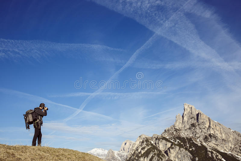 Fotógrafo del caminante que toma las fotos en un top de la montaña foto de archivo