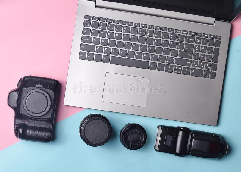 Fotógrafo del equipo, ordenador portátil, monedero con los dólares, en un fondo en colores pastel azul rosado Concepto independie foto de archivo