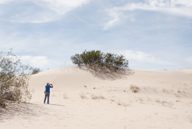 Fot?grafo del hombre de la duna de arena del paisaje del desierto fotos de archivo