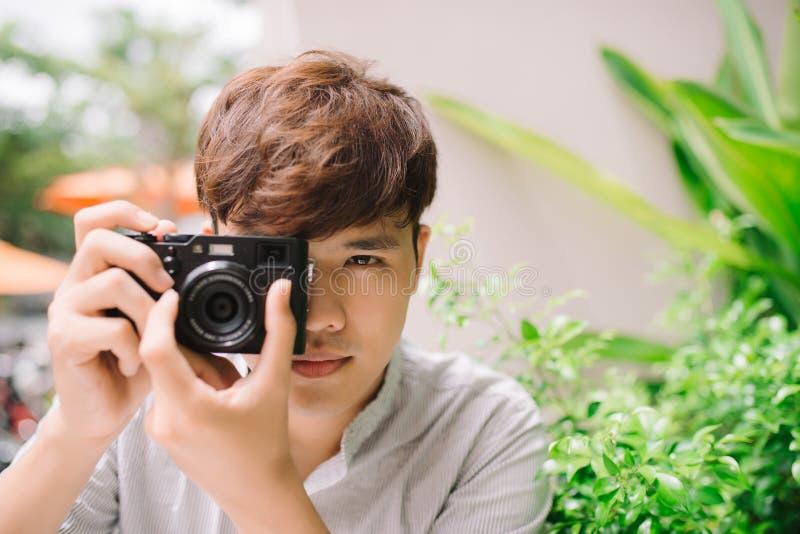 Fotógrafo del hombre joven que toma la imagen que se sienta en la tabla en café foto de archivo