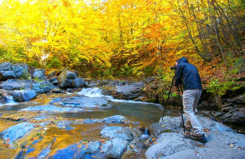 Fotógrafo del paisaje que toma imágenes en la estación del otoño imagen de archivo libre de regalías