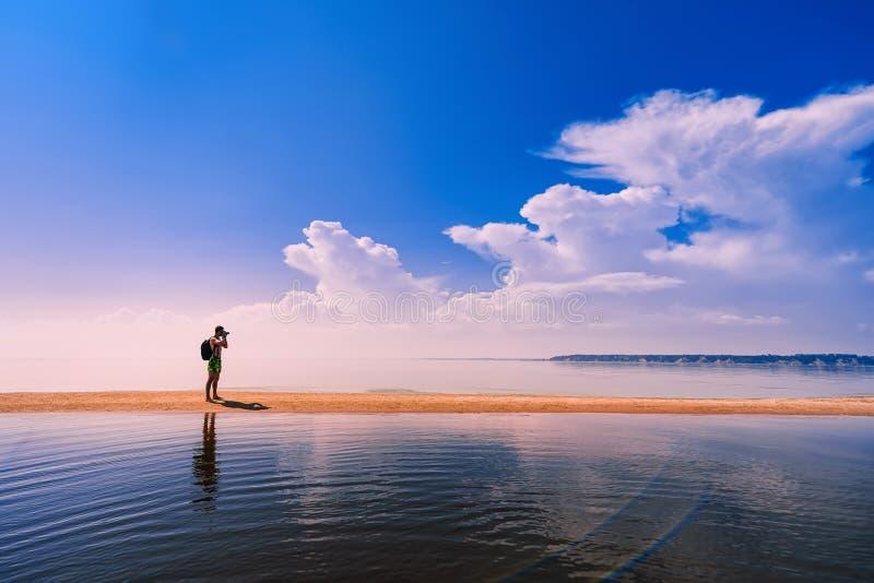 Fotógrafo del viajero con la mochila que toma las imágenes del mar en descanso imagen de archivo libre de regalías