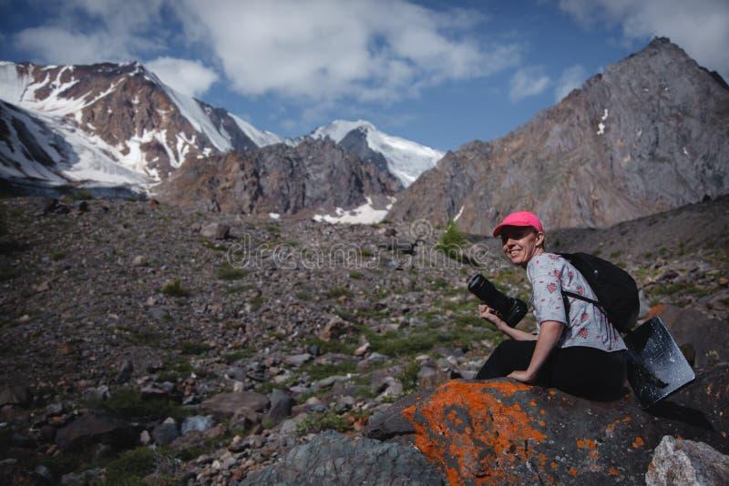 Fotógrafo del viajero de la muchacha con una cámara que se sienta en una piedra que goza de las montañas de Altai concepto del re imagen de archivo