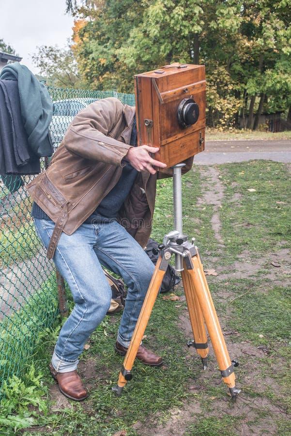 Fotógrafo do artista com a câmera da placa molhada no tripé imagem de stock