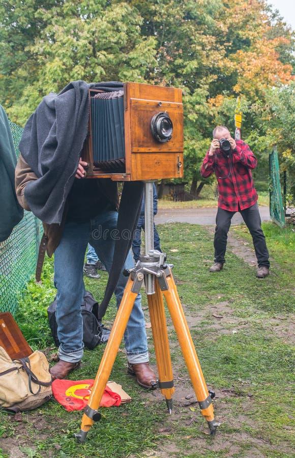 Fotógrafo do artista com a câmera da placa molhada no tripé fotografia de stock