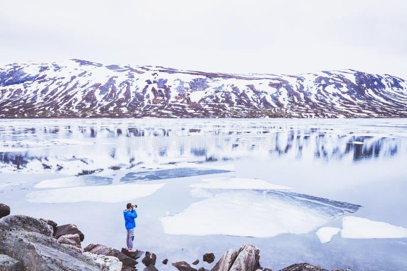 Fotógrafo do curso que toma a foto da paisagem nevado em Noruega na mola imagens de stock royalty free