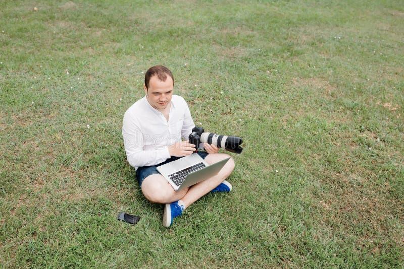 Fotógrafo do homem novo que usa o portátil e a câmera no parque fotografia de stock royalty free