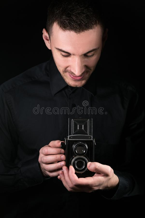 Fotógrafo do homem que guarda uma câmera Processo de tiro Câmera de reflexo média da gêmeo-lente do formato da câmera retro da fo imagens de stock royalty free