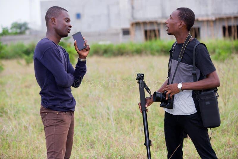 Fotógrafo dois masculino novo que conversa junto na natureza imagem de stock