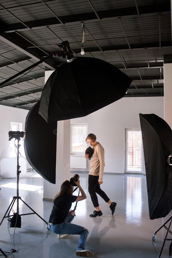 Fotógrafo e modelo durante a sessão do estúdio imagem de stock