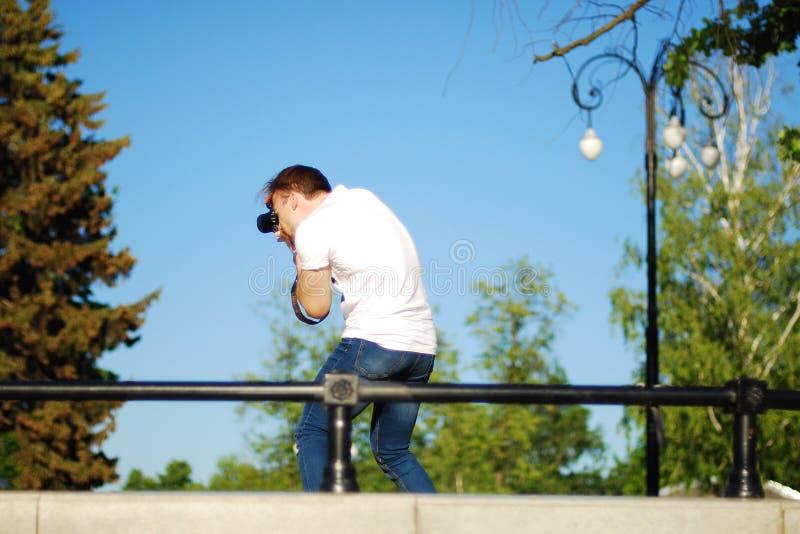 Fotógrafo en el trabajo en el parque de la ciudad, sesión fotográfica en naturaleza imagen de archivo libre de regalías