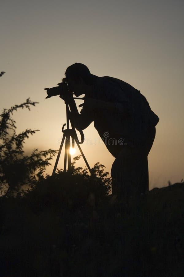 Fotógrafo en silueta de la acción imagen de archivo