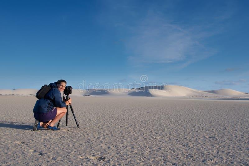 Fotógrafo fêmea que toma a foto da paisagem de dunas de areia fotografia de stock