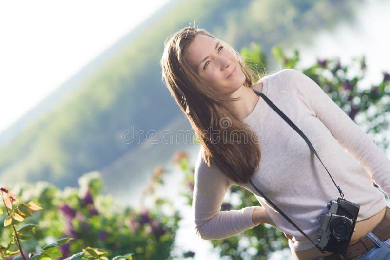 Fotógrafo feliz de la mujer joven que usa la cámara vieja imagenes de archivo