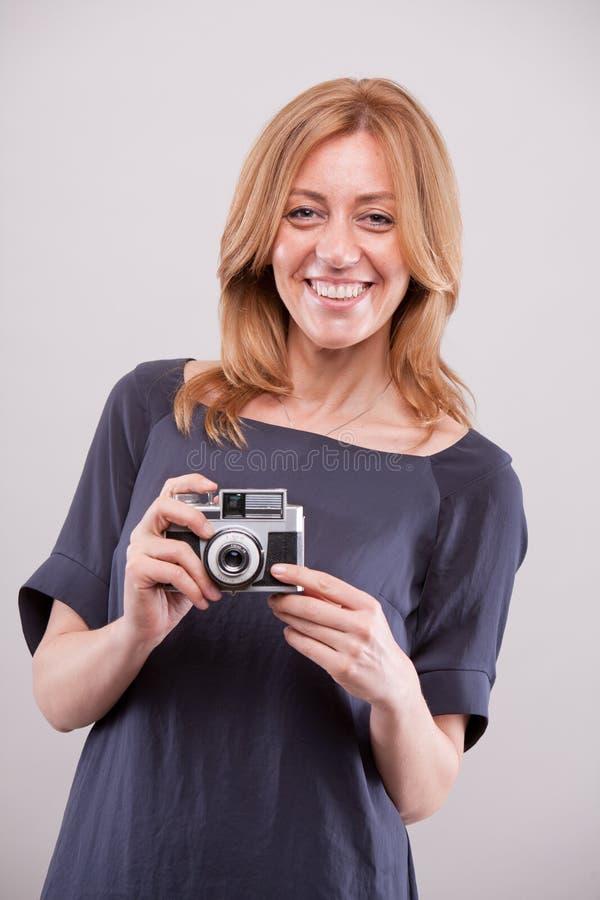 Fotógrafo feliz de la mujer que sonríe a usted fotografía de archivo