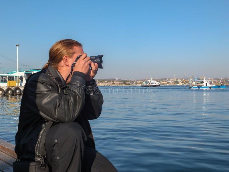 Fotógrafo hermoso joven del hombre con el pelo largo rubio en chaqueta de cuero negra contra bahía azul del mar de las fotografía foto de archivo