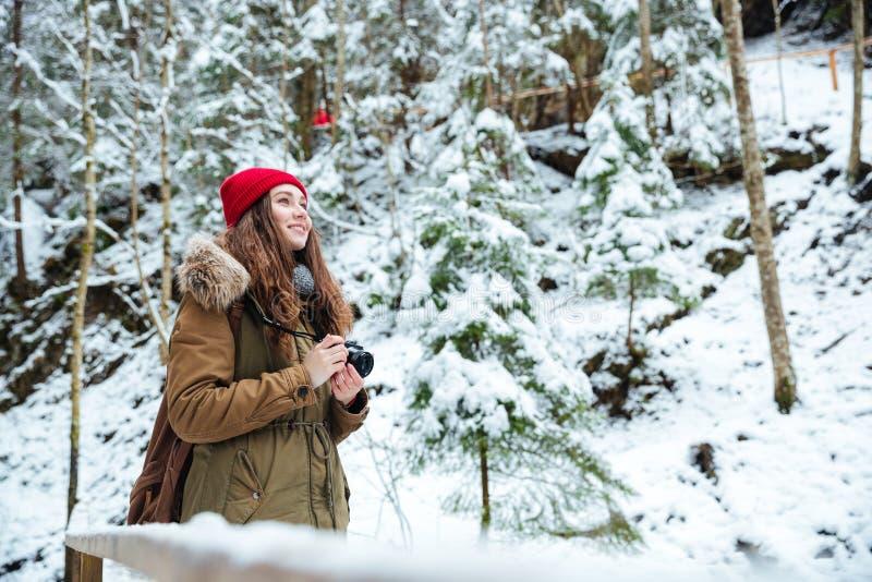 Fotógrafo inspirado de sorriso da mulher que toma fotos na floresta no inverno fotos de stock