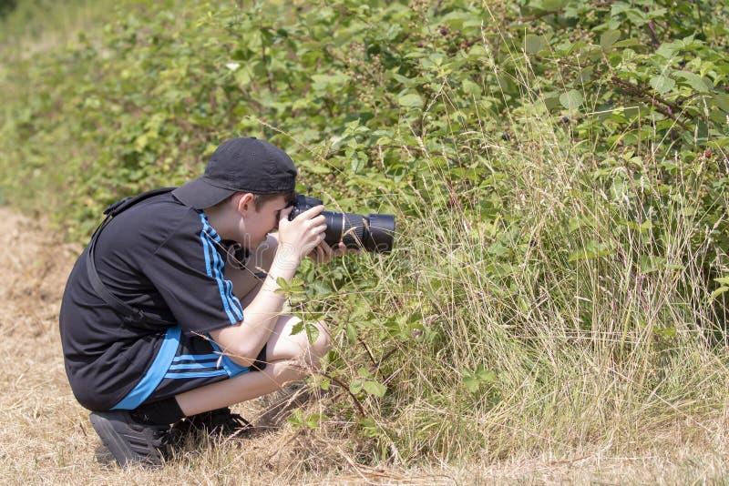 Fotógrafo joven del muchacho que fotografía la naturaleza foto de archivo libre de regalías