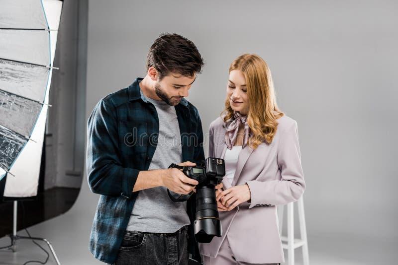 fotógrafo joven hermoso y muchacha sonriente hermosa que usa la cámara de la foto junto imagen de archivo libre de regalías