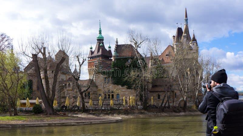 Fotógrafo joven que fotografía el castillo de Vajdahunyad imagenes de archivo