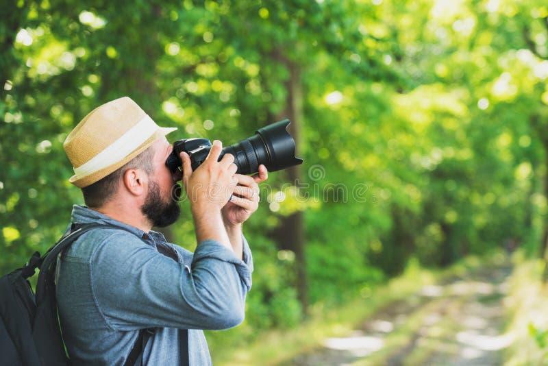 Fotógrafo masculino com trouxa e câmera que toma uma foto Férias do active da aventura do conceito do passatempo do estilo de vid imagem de stock
