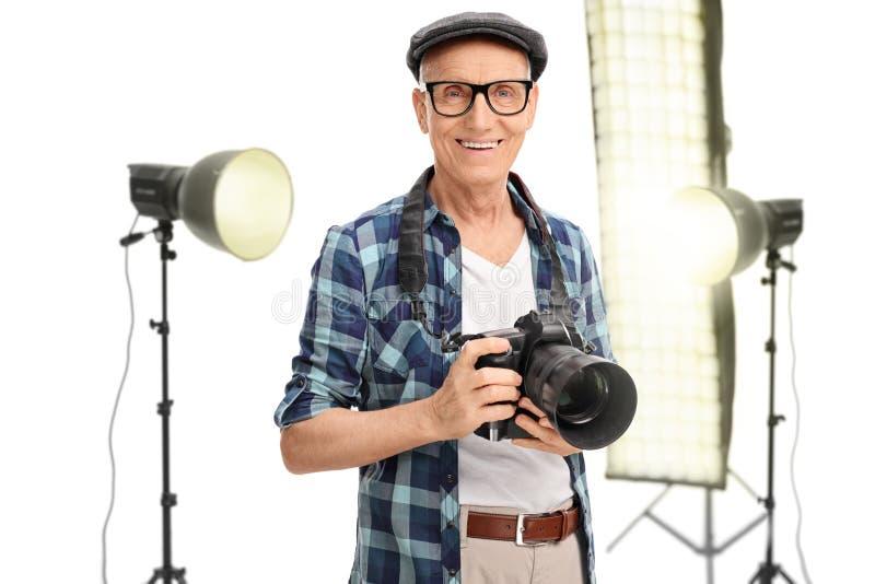 Fotógrafo mayor que se coloca en un estudio fotos de archivo