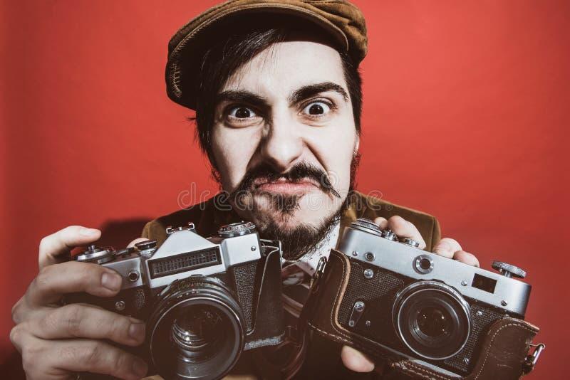 Fotógrafo muito positivo que levanta no estúdio com câmeras imagens de stock