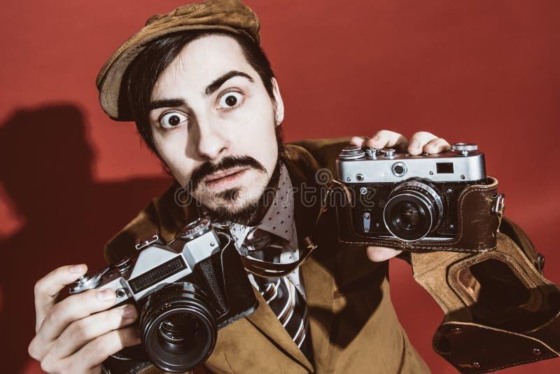 Fotógrafo muy positivo que presenta en estudio con las cámaras imagen de archivo libre de regalías