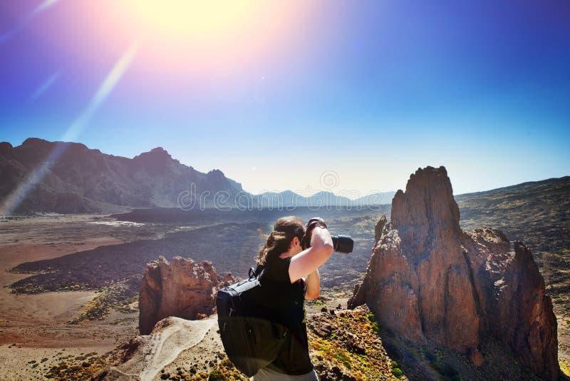 Fotógrafo na ação com sua equipe durante o por do sol na montanha rochosa Conceito do curso da aventura tenerife fotografia de stock royalty free