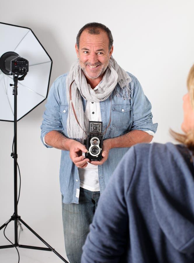 Fotógrafo no estúdio que toma tiros do modelo da mulher fotos de stock
