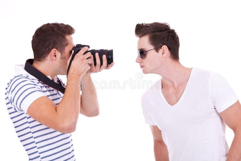 Fotógrafo novo durante um tiro de foto foto de stock