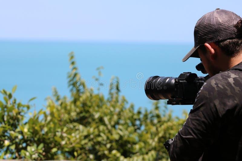 Fotógrafo ou videographer que guardam a câmara de vídeo em um tripé sobre a montanha fotografia de stock royalty free