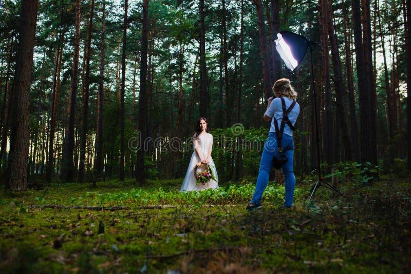 Fotógrafo profesional de la boda que usa el estroboscópico y el softbox para hacer imágenes fotografía de archivo