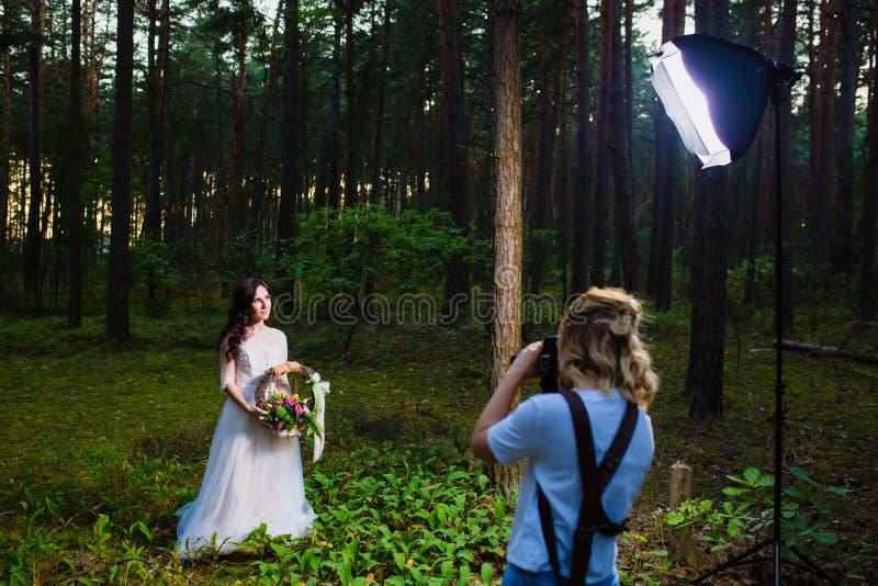 Fotógrafo profesional de la boda que usa el estroboscópico y el softbox para hacer imágenes foto de archivo libre de regalías