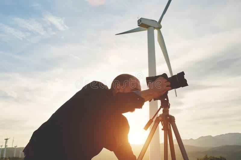 Fotógrafo profesional de sexo masculino que toma la foto en la cámara digital mientras que se opone al molino de viento y a la pu imagen de archivo libre de regalías