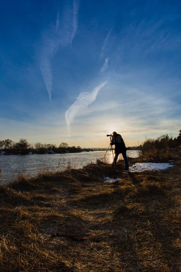 Fotógrafo profesional que toma un río de la inundación de la foto foto de archivo