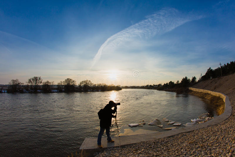 Fotógrafo profesional que toma un río de la inundación de la foto en la puesta del sol fotos de archivo libres de regalías