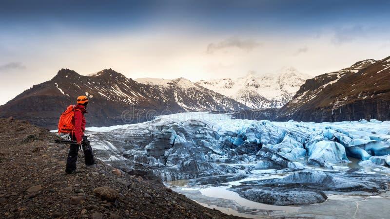 Fotógrafo profissional com câmera e tripé no inverno fotógrafo profissional que olha à geleira em Islândia imagens de stock royalty free
