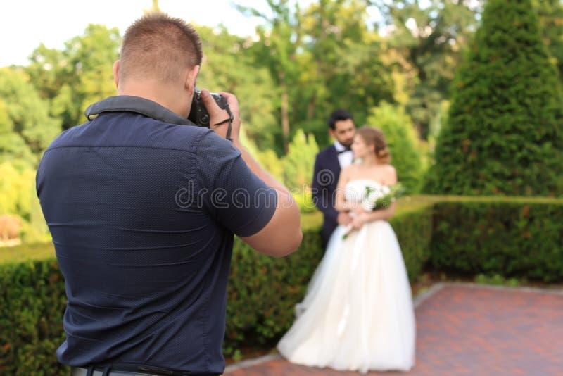 Fotógrafo profissional que toma a foto de pares do casamento fora fotografia de stock royalty free