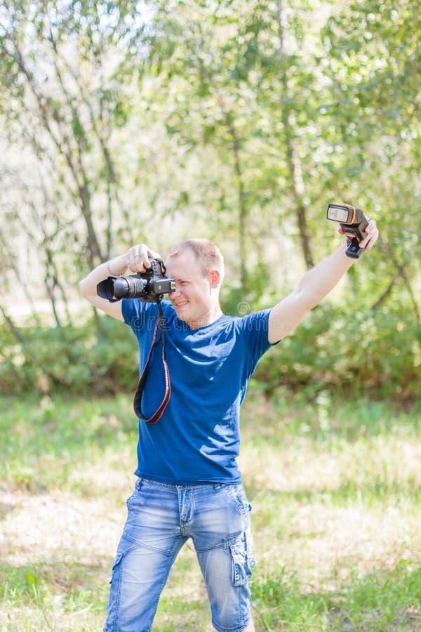 Fotógrafo que lleva la camiseta azul que trabaja al aire libre Árbol en campo Hombre joven con un equipo de la cámara y de la luz fotografía de archivo