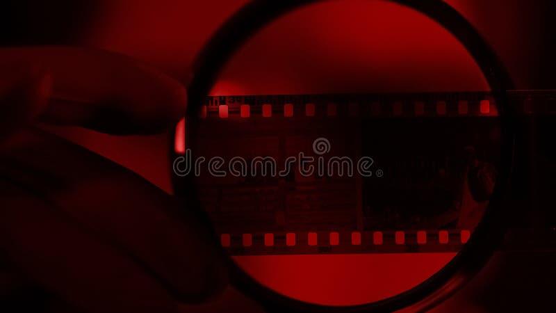 Fotógrafo que mira el rollo de la cámara a través de la lupa, sitio ligero rojo fotografía de archivo