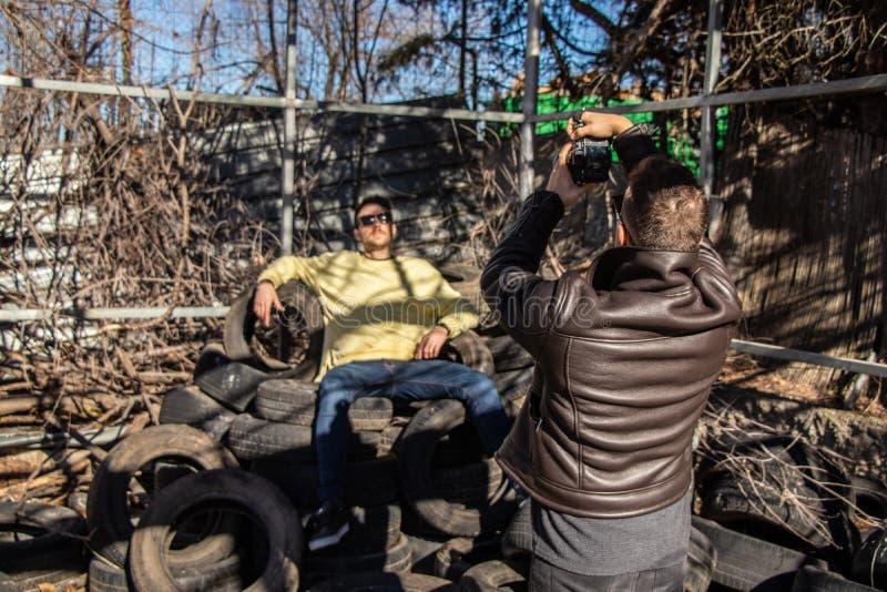 Fotógrafo que retrata un modelo con el equipo urbano en una montaña de neumáticos fotografía de archivo libre de regalías