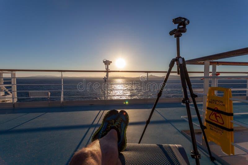 Fotógrafo que se relaja antes de comenzar el trabajo en la puesta del sol en una cubierta superior del barco de cruceros imagenes de archivo
