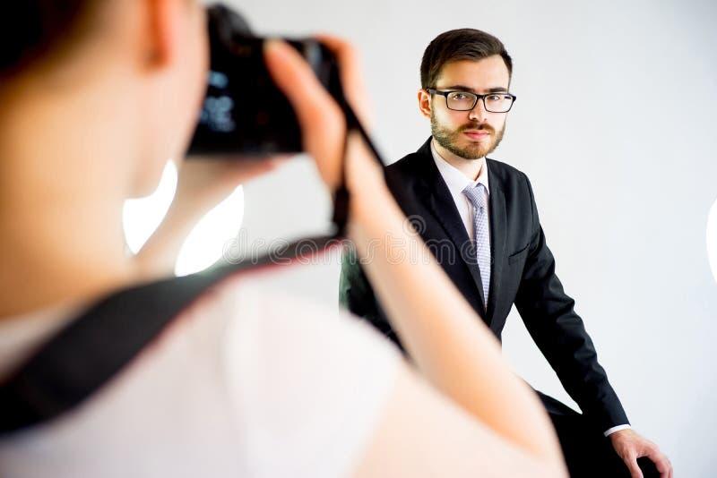 Fotógrafo que toma a imagem de um modelo no estúdio foto de stock