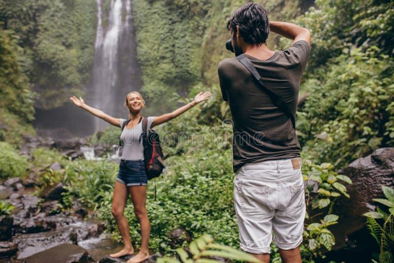 Fotógrafo que toma las fotos de una mujer cerca de la cascada foto de archivo