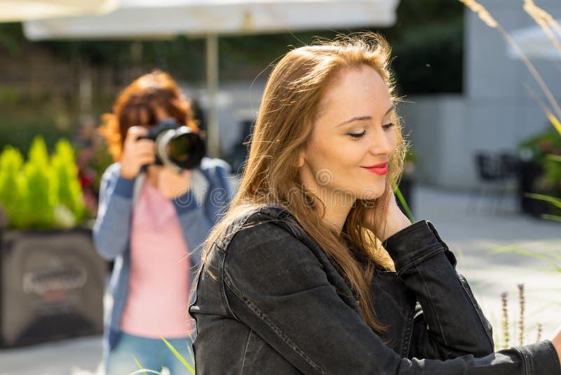 Fotógrafo que toma las imágenes de la mujer al aire libre imagen de archivo